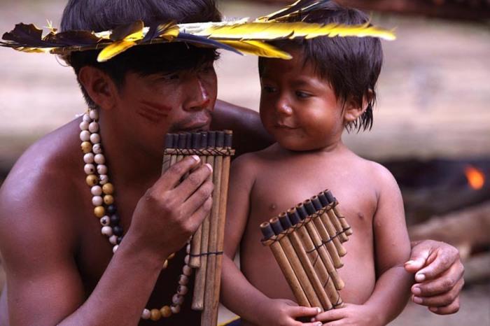 Indio ensinando o filho a tocar sua flauta